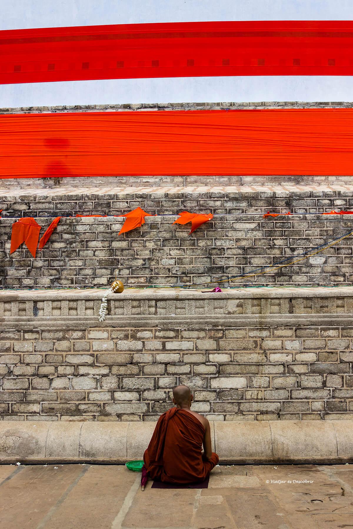 Monjo resant al voltant d'una stupa
